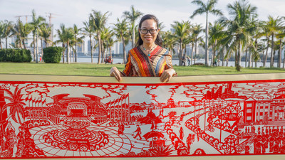 Huang Haitao, who led the papercut team, shows the part of the 22-meter scroll depicting the Boao Forum for Asia conference.